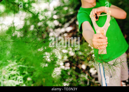 Boy threatening his schoolmates with a slingshot. - Stock Photo