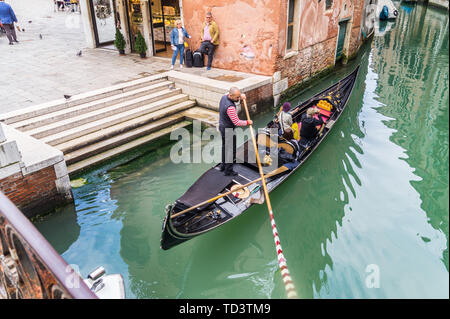 Tourists in a gondola and on land waiting for a water taxi, Campo Santi Apostoli, Cannaregio, Venice, Veneto, Italy - Stock Photo
