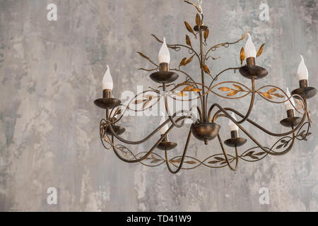 luxurious black metal chandelier hanging on the ceiling.contemporary chandelier, is a branched ornamental light fixture designed to be mounted on - Stock Photo
