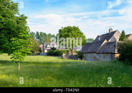 Cotswold stone houses in Wyck Rissington in the late evening light, Cotswolds, Gloucestershire, England - Stock Photo