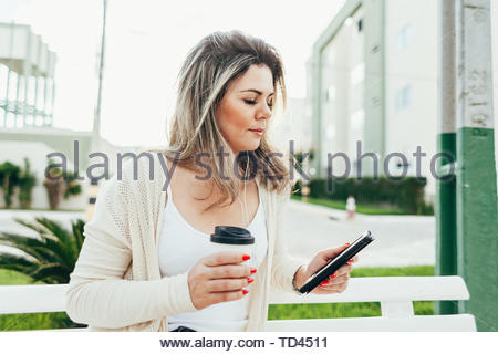 A young woman sits on a bench, holds a coffee cup in her hand and reads an e-book in the city - Stock Photo