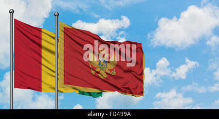 Guinea and Montenegro flag waving in the wind against white cloudy blue sky together. Diplomacy concept, international relations. - Stock Photo