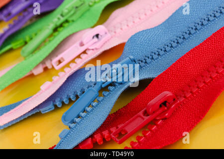 Multicolored zippers on yellow background - Stock Photo