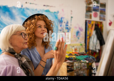Teacher in glasses. Art teacher in glasses feeling satisfied with work of her young red-haired student - Stock Photo