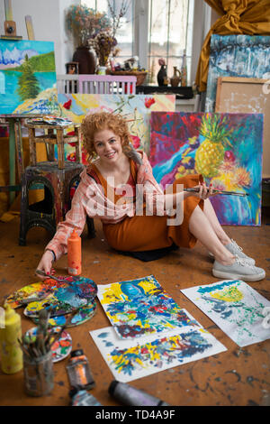 Famous artist. Top view of young famous artist sitting on floor near her different nice pictures - Stock Photo
