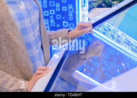 Woman using multimedia touchscreen display of interactive kiosk - Stock Photo