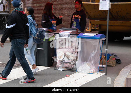 Princeton, New Jersey - April 28, 2019: College students were seen at a street fair making sure that the people put their trash in the correct trash r - Stock Photo