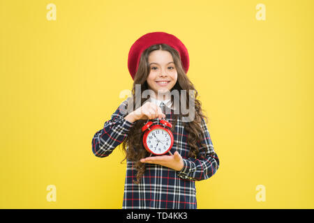 Retro is timeless. Happy small child holding retro clock on yellow background. Little girl smiling with retro design clock. Adorbale kid with vintage clock in retro style. - Stock Photo