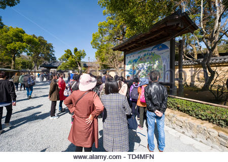 Group of tourist listening to male guide in front of a large illustrated map at the entrance to Kinkaku-ji Buddhist temple - Stock Photo