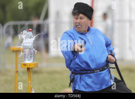 Chelyabinsk, Russia. 12th June, 2019. MOSCOW REGION, RUSSIA - JUNE 12, 2019: A man in a Cossack costume shows his sword skills at Russky Mir Festival in the town of Sergiyev Posad on 12 June, known as Russia Day. Mikhail Japaridze/TASS Credit: ITAR-TASS News Agency/Alamy Live News - Stock Photo