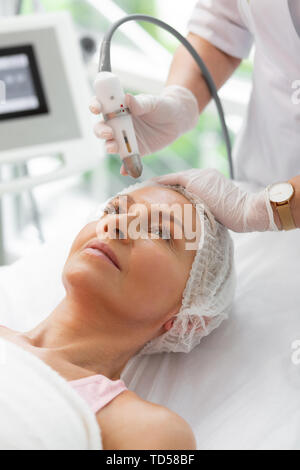 Female beauty. Positive aged woman receiving a beauty procedure while visiting a cosmetologist - Stock Photo