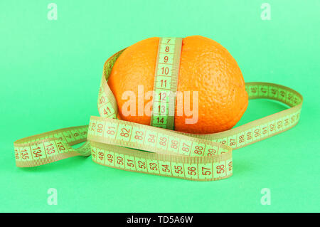 Orange with measuring tape, on color background - Stock Photo