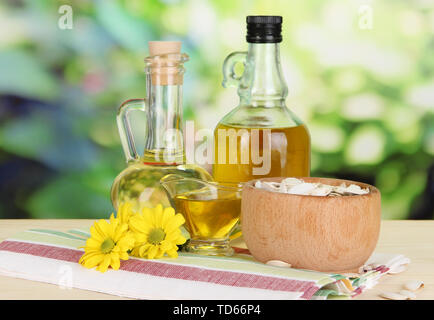 Useful pumpkin seed oil on wooden table on natural background - Stock Photo