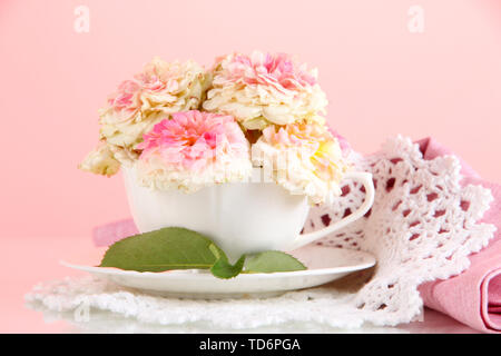 Roses in cup on napkins on pink background - Stock Photo