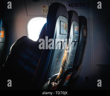 United Kingdom - Nov 14, 2017: Rear view of woman sleeping on the airplane seat with red hairs falling thourhg the passengers seats - Stock Photo