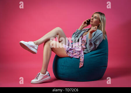 Beautiful blonde girl in a blue jacket and a purple sundress sits on a green bag chair with her legs folded on a pink isolated background and talking  - Stock Photo