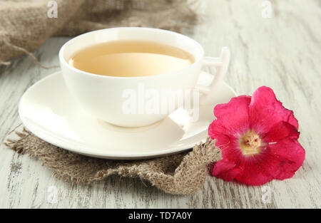 Cup of tea and pink mallow flower on wooden background - Stock Photo