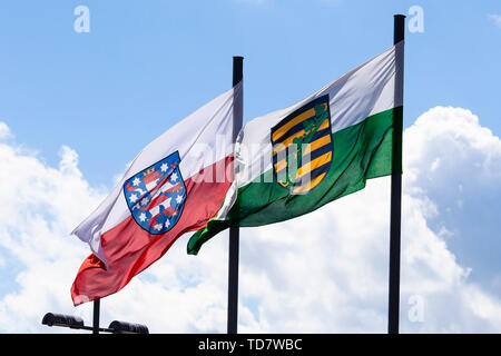 Kiel, Germany. 13th June, 2019. The flags of the Free State of Thuringia (l) and the Free State of Saxony blow in the wind. At their spring conference on 13 June, the Interior Ministers of the Federal Government and the Länder will discuss police operations at football matches and better cooperation in the fight against clan structures. A total of 69 topics are on the agenda of the meeting, which will run until June 14. Credit: Frank Molter/dpa/Alamy Live News - Stock Photo