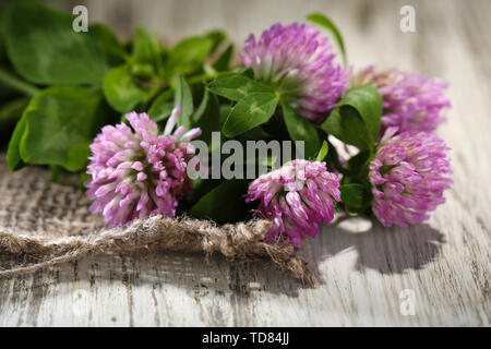 Clover flowers with leaves on wooden background - Stock Photo