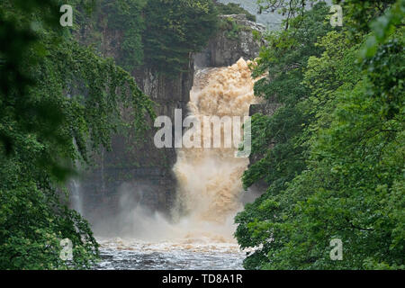 Water gushes over the High Force Waterfall on the River Tees in Teesdale, near Middleton-in-Teesdale in the Northern Pennines after days of heavy rainfall across the UK. - Stock Photo