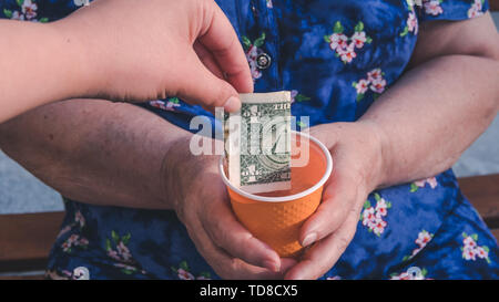 Old woman begs for alms. Closeup of money and coins in hand of poor woman. Social problems of society - Stock Photo