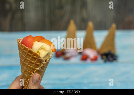 Sweet ice cream in balls on a wooden background. Dessert with different flavors and fresh berries and fruits. Ice cream in a waffle cone. Copy space - Stock Photo