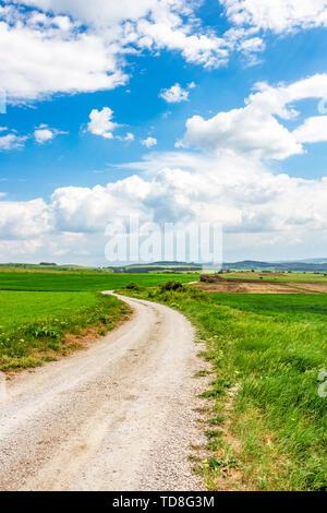 Empty Bulgarian country dirt road winding between green May fields under beautiful cloudy sky at the village of Chukovezer - Stock Photo