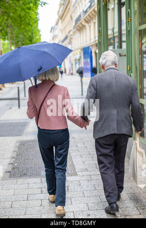 Elderly couple under umbrella holding hands. Loving each other old people go down the street. - Stock Photo