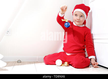 A little boy in the shape of Santa Claus is smiling, stands on a white background, and holds a Christmas toy in his hand - Stock Photo