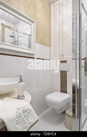 Soap dispenser and folded towel next to sink on wooden countertop in attic bathroom   UK & IRISH USE ONLY - Stock Photo