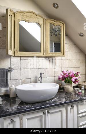 Trifold wooden mirror above washbasin on black marble countertop in attic bathroom   UK & IRISH USE ONLY - Stock Photo