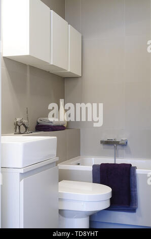 Violet towels draped over bathtub rim in minimalist bathroom   UK & IRISH USE ONLY - Stock Photo