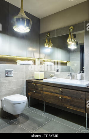 Large yellow square candle on wooden countertop next to washbasin in modern bathroom   UK & IRISH USE ONLY - Stock Photo