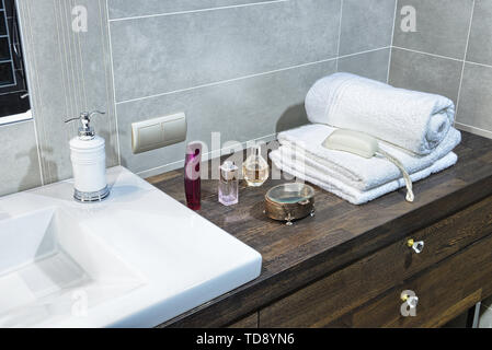 White towels and perfumes on wooden countertop next to washbasin in modern bathroom   UK & IRISH USE ONLY - Stock Photo