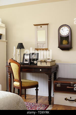 Framed family pictures and table lamp on brown side table in bedroom   UK & IRISH USE ONLY - Stock Photo