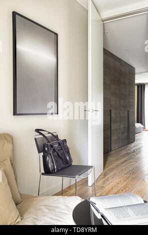 Leather handbag on metal chair in work room next to hallway entrance   UK & IRISH USE ONLY - Stock Photo