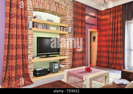 TV and audio video equipment on recessed brick wall shelves in modern living room    UK AND IRISH RIGHTS ONLY - Stock Photo