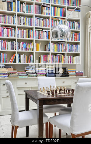 Dark brown chess table with white chairs in front of hanging bookcase above chest of drawers in orangery    UK AND IRISH RIGHTS ONLY - Stock Photo