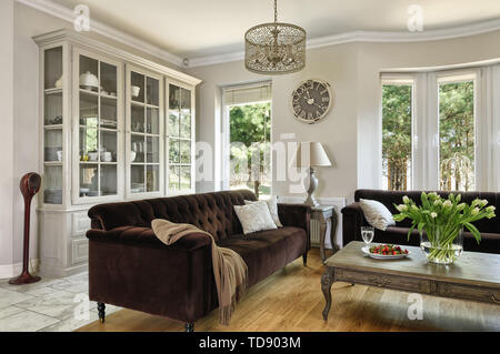 Wooden coffee table in front of two tufted sofas in living room    UK AND IRISH RIGHTS ONLY - Stock Photo
