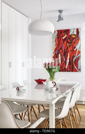 Ceramic tableware and red tulips bouquet on white glossy dining table   UK & IRISH USE ONLY - Stock Photo