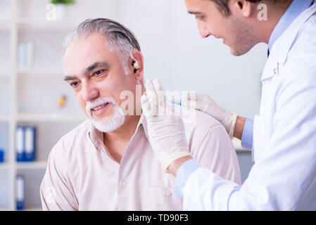Male patient with hearing problem visiting doctor otorhinolaryngologist - Stock Photo