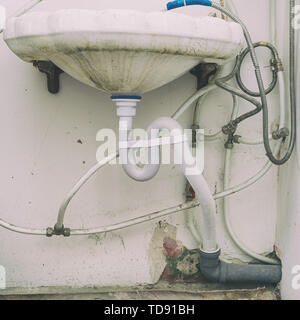 Dirty sink with wrong connection of pipes and other plumbing - Stock Photo