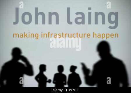 The John Laing logo is seen on an LED screen in the background while a silhouetted person uses a smartphone in the foreground (Editorial use only) - Stock Photo