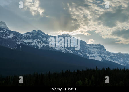 Sun breaking through clouds over mountains at dusk - Stock Photo