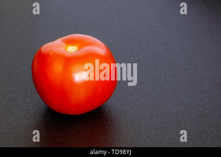 Red ripe tomato on a black texture background - Stock Photo
