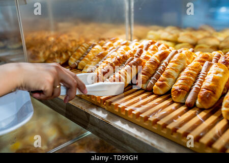 Closeup of woman hand using clamp to pick sausage sandwich - Stock Photo