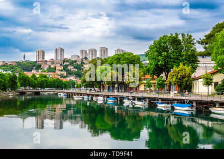 Rijeka, Croatia: Rjecina river in the city center with boats and view over the city - Stock Photo