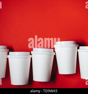 Several paper cups for coffee or tea on red background. Copy space for text. - Stock Photo