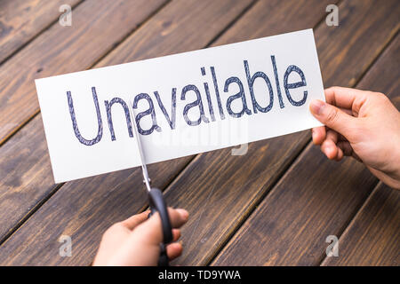 woman cuts white paper with word unavailable on table - Stock Photo