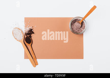 Homemade anti-cellulite coffee scrub with sea salt near jar of fresh made product on white background, flat lay mockup. - Stock Photo